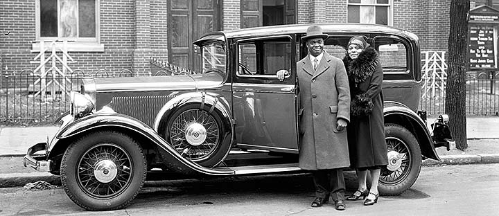 African American couple standing in front of a car, circa 1926