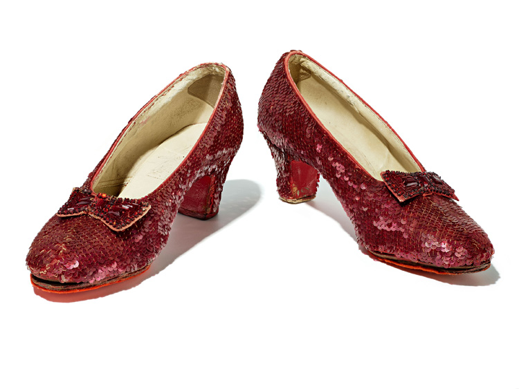 Pair of red shoes covered in sequins. Small heels. Bow.