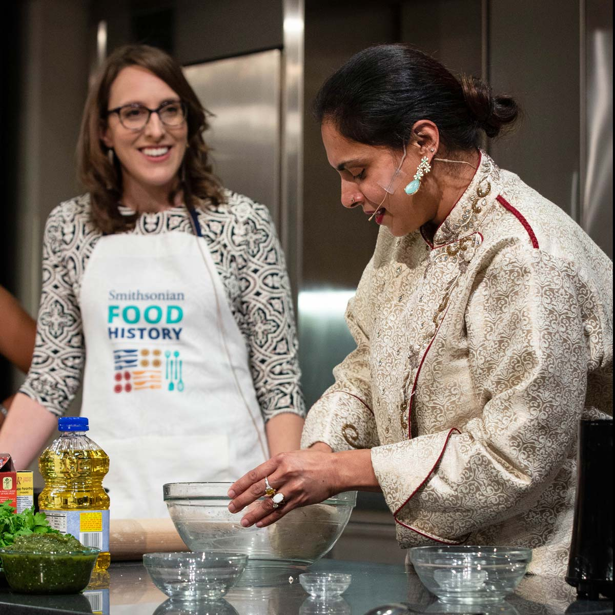 Photo of chef Maneet Chauhan at a live cooking demonstration with food historian Ashley Rose Young