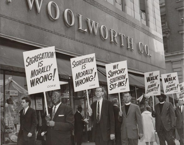 Marchers in front of a Woolworth's with signs