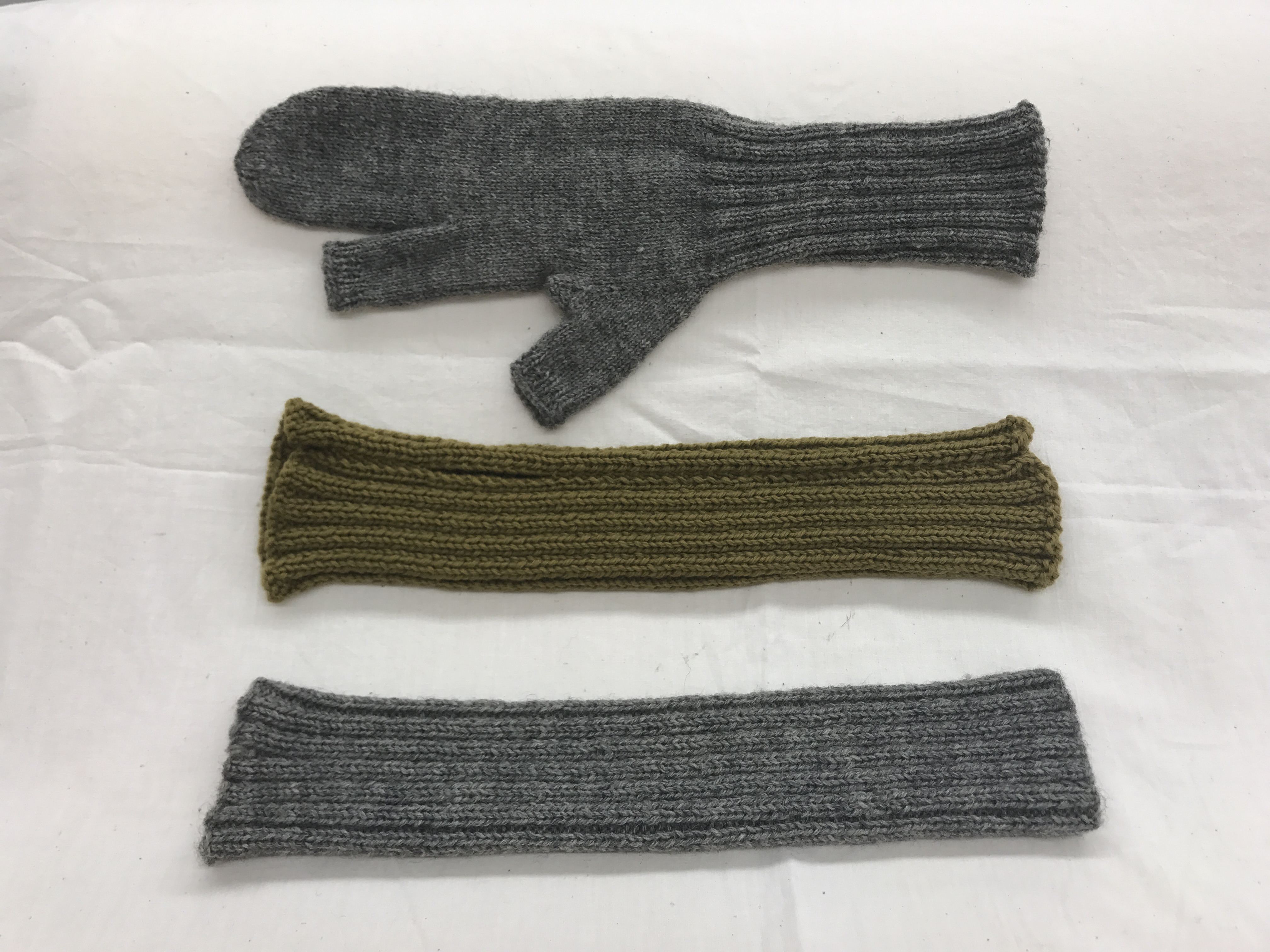79c76904 Three knitted items in Army green and grey. One is mitten-shaped. Two