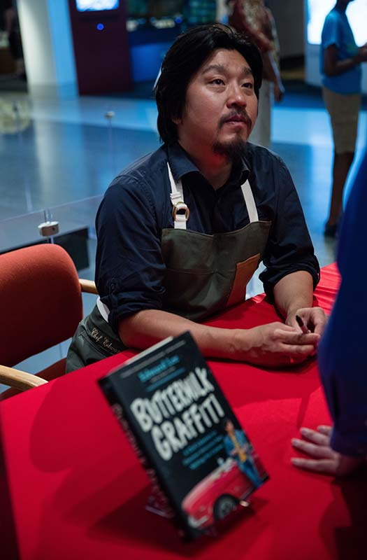 "Chef Lee, wearing an apron, sits at a table with a red table cloth. Beside him, his book ""Buttermilk Graffiti."" He looks up to listen to a visitor (unseen) who is getting their book signed."