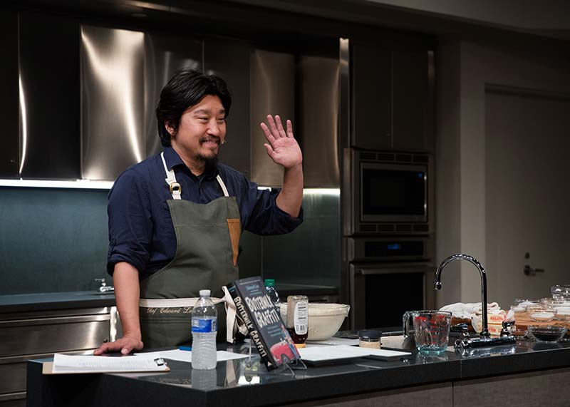 Leaning on a kitchen counter covered in bowls, a jar of honey, a measuring cup, and other kitchen items, Chef Lee smiles and waves at an unseen audience. He has a beard, black hair, and a smile. Behind him, shiny cabinets. On the counter, his book.