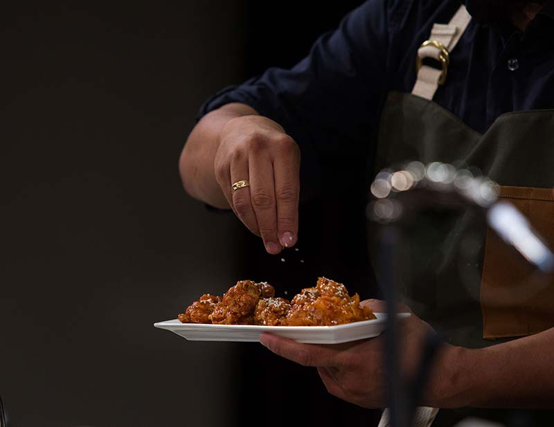 Close up on a hand spicing or salting a dish of beautiful fried chicken. It's golden and crispy. The spices or salt falling out of the hand are chunky and white. The chef is wearing an apron.