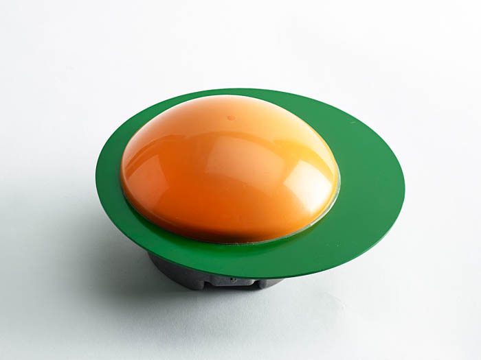A plastic contraption with one green oval and one yellow oval.