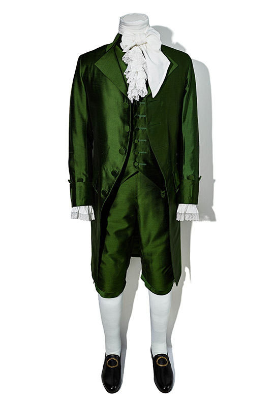 A shiny green suit, comprised of three pieces: knee length pants, a vest, and waistcoat. Around the collar is a bow and a cravat.