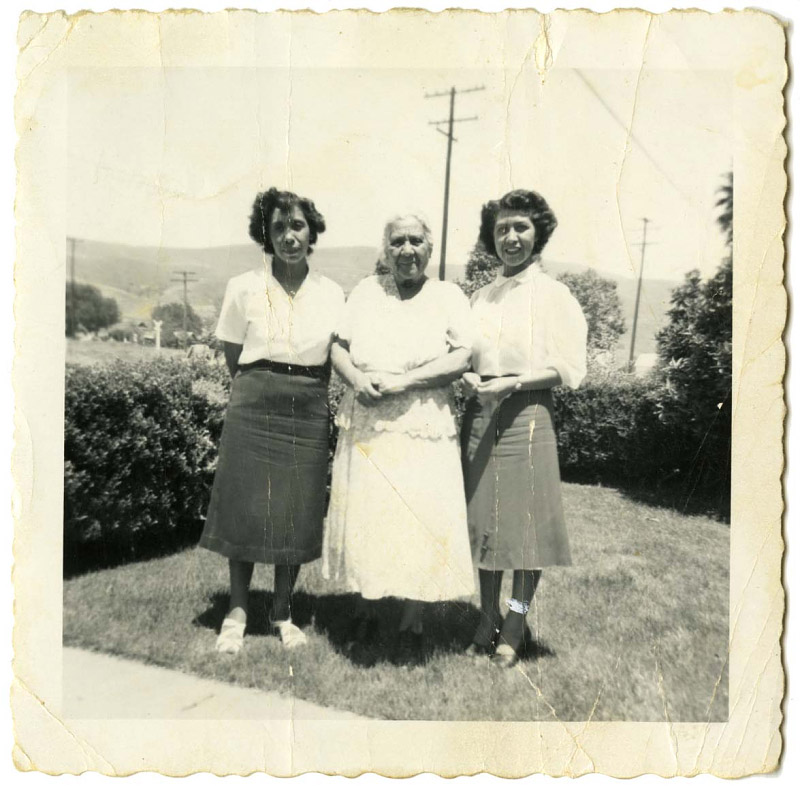 A black and white photograph. An older woman in a light color dress stands in the middle of two younger women, wearing 1950s style clothing.