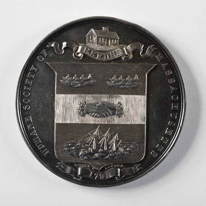 A silver medal engraved with a crest featuring boats and enclasped hands, the edge reads Humane Society of Massachusetts, Refuge, 1791