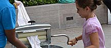 A child experimenting with a historic laundry device