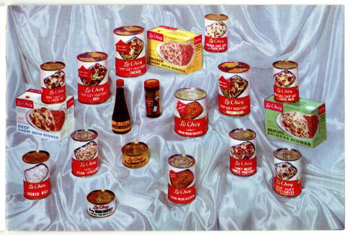 Different LaChoy products sit arranged on a silky background. They include soy sauce and canned and boxed foods.