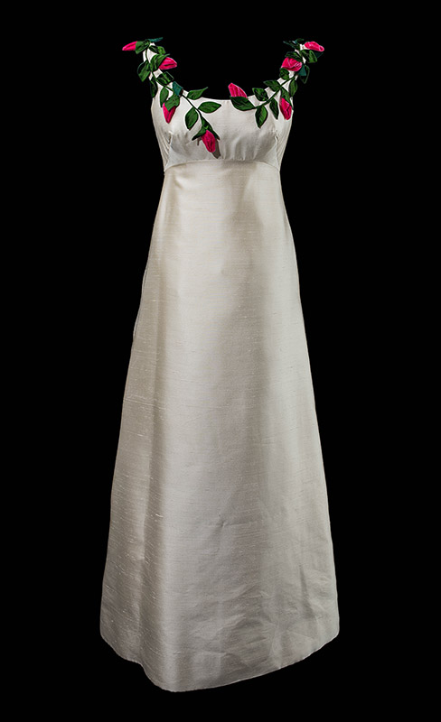 A white dress, the fabric has a sheen, around the top are flowers made of velvet and satin.
