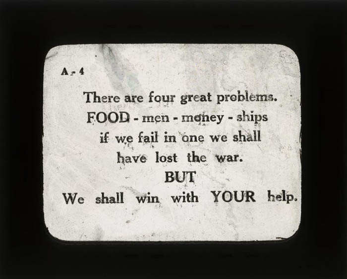 "A magic lantern slide reading ""There are four great problems. FOOD- men- money- ships if we fail in one we shall have lost the war. BUT We shall win with YOUR help."""