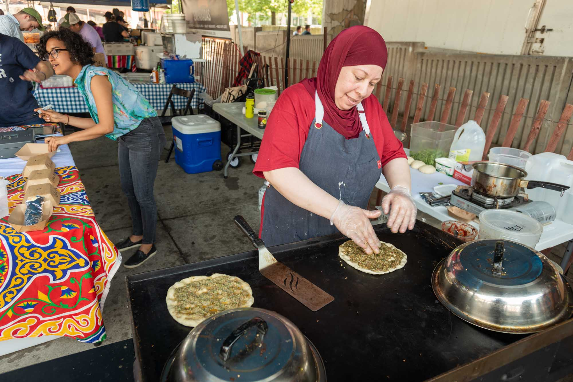 Chef Iman, featured in the photo above, arrived in the United States from Syria as a widow, without family accompanying her. As a member of the Mera Kitchen Collective, she prepares dishes from Syria for sale at the Baltimore Farmer's Market. Photo by Car