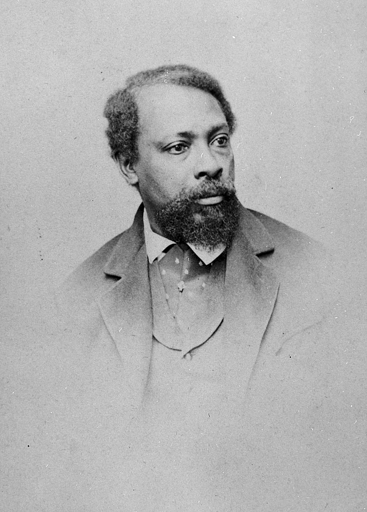 A black and white photograph of David Bustill Bowser. The photo is vignetted, focusing on just his bust. He wears his hair parted to one side, and dons a mustache and beard. He also wears a coat, vest, and collared shirt. The shirt is patterned.