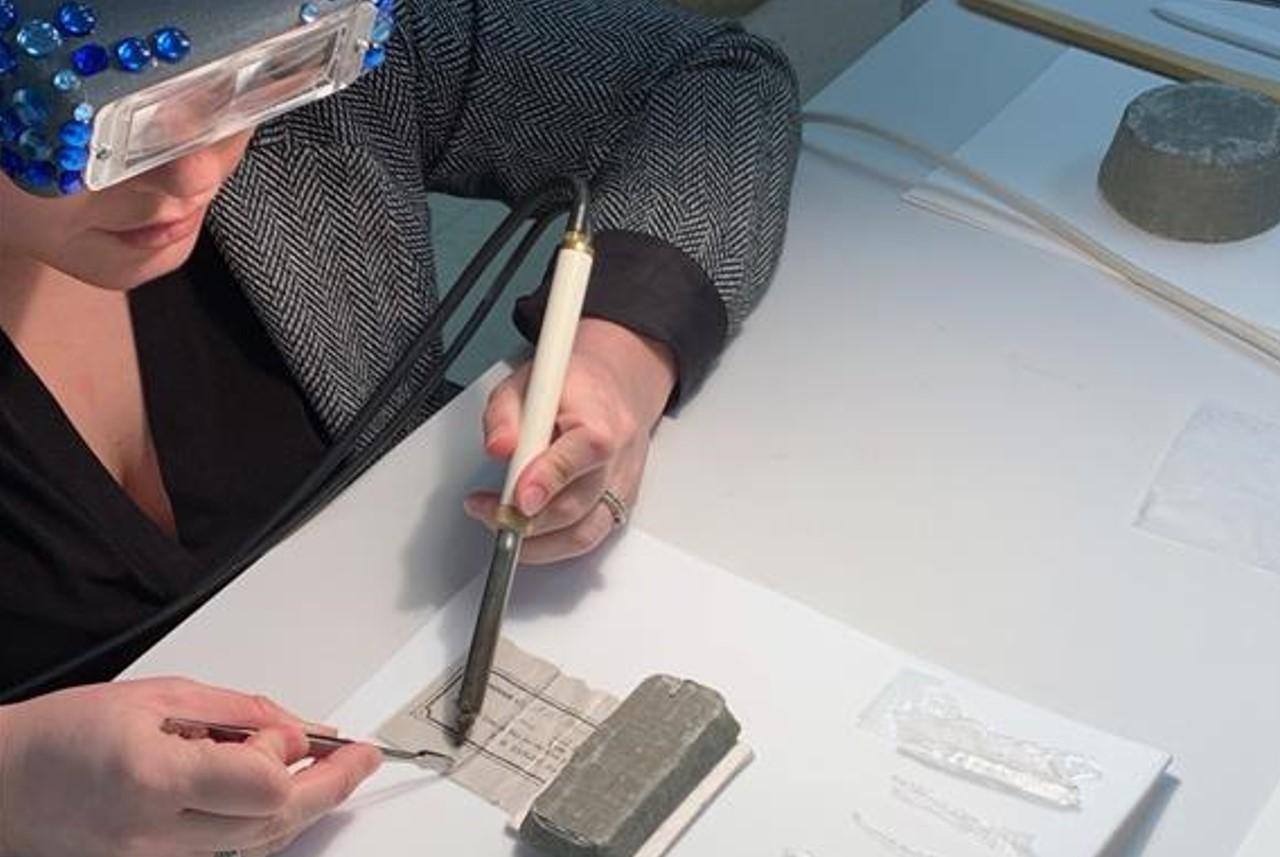 A conservation technician removes lamination from a paper document using a heat pencil and tweezers.