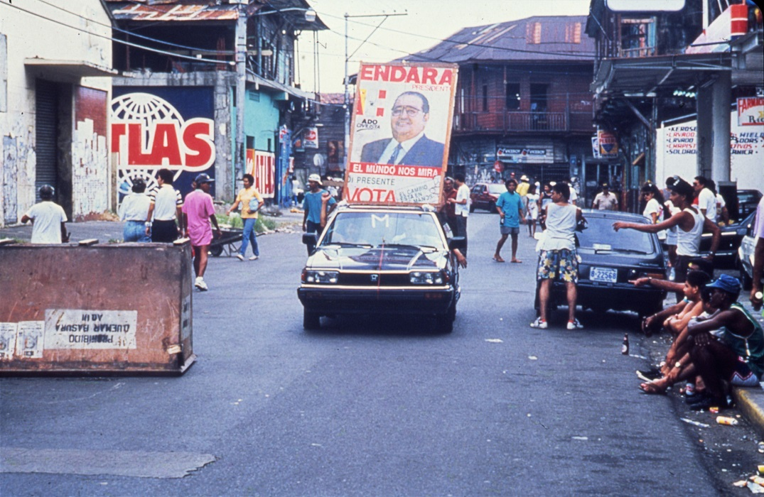 A photograph of a car traveling a city street with a poster featuring a man on it.