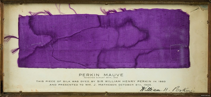 A piece or rich purple silk in a frame