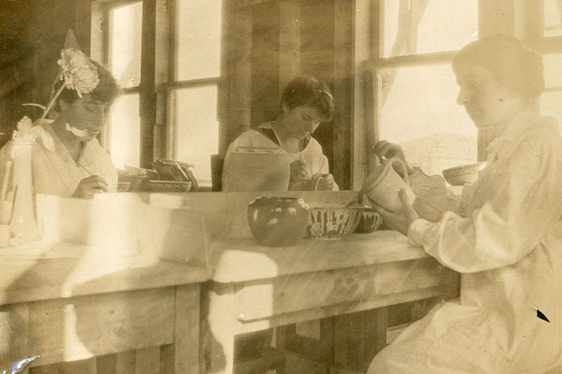 A sepia colored photograph of women working on the pottery.
