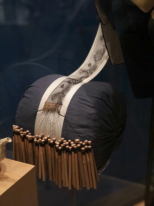 Black lace, still attached to the bobbins used to create it, is draped over a pillow.
