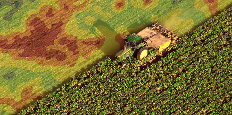 An image of a tractor or combine in the field. Overlayed graphically is a read out from a precision farming mechanism.