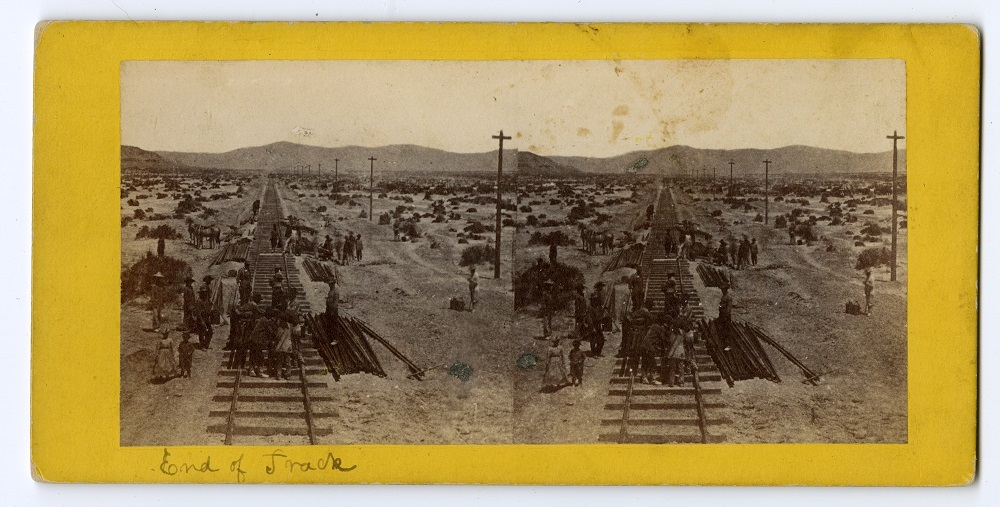 Identical photographs side by side in which men stand on train tracks and look into the horizon