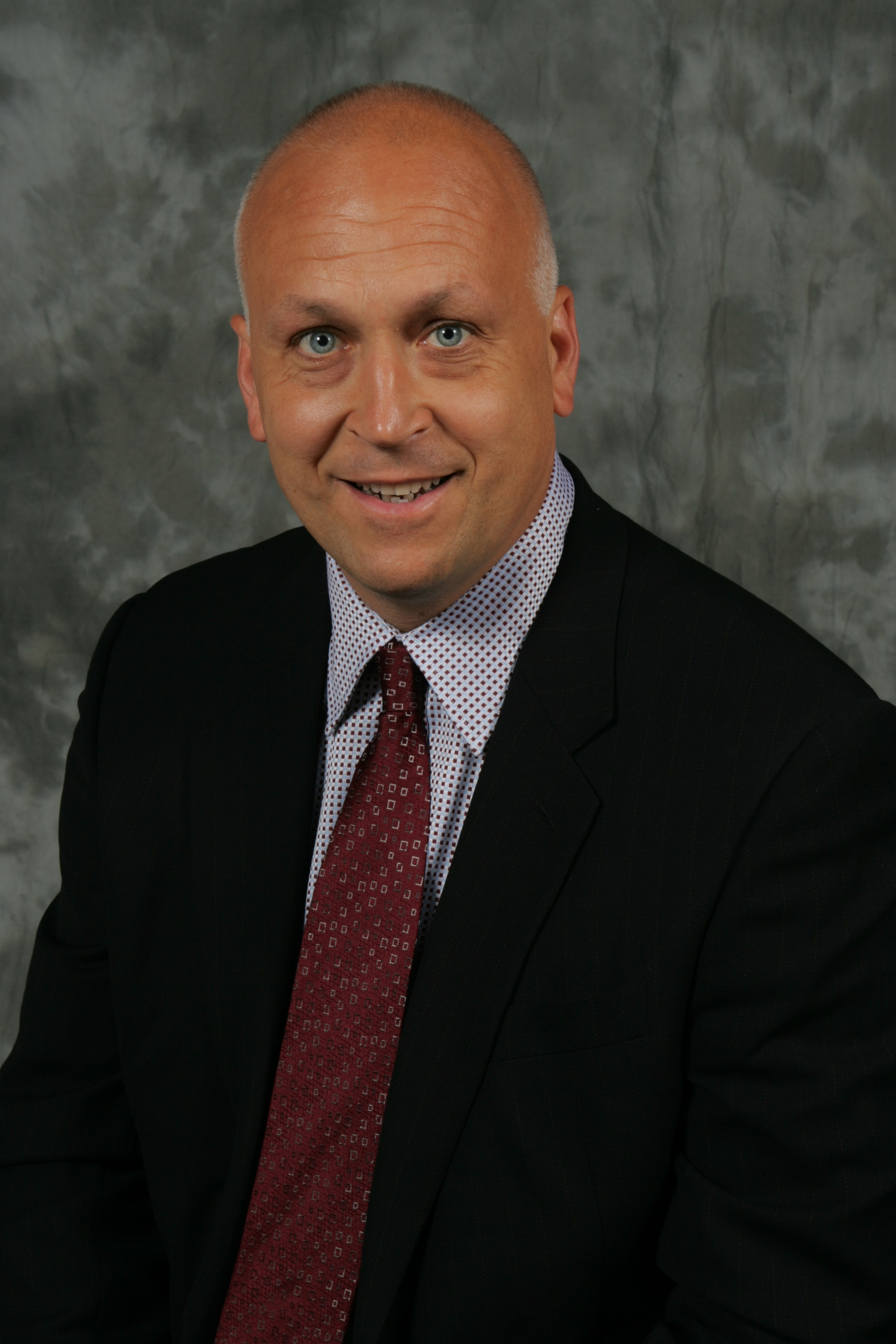 A photograph headshot of a sitting man in a suit