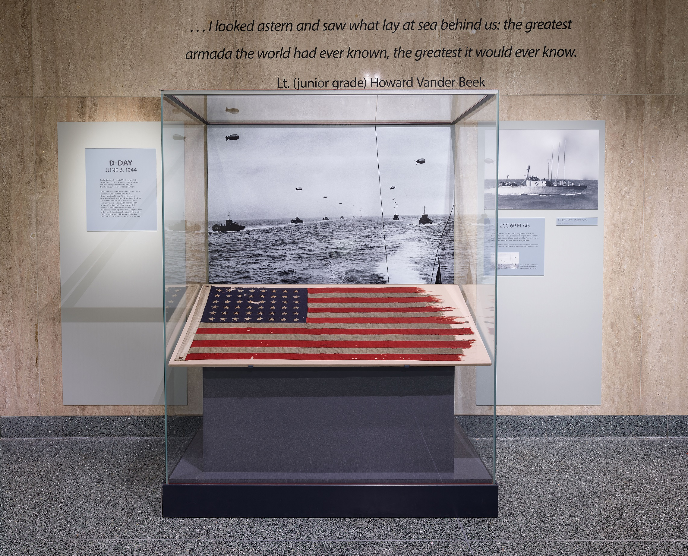 A flag sits in a glass case against a stone wall on which there is a quote. Signage and images are also visible.