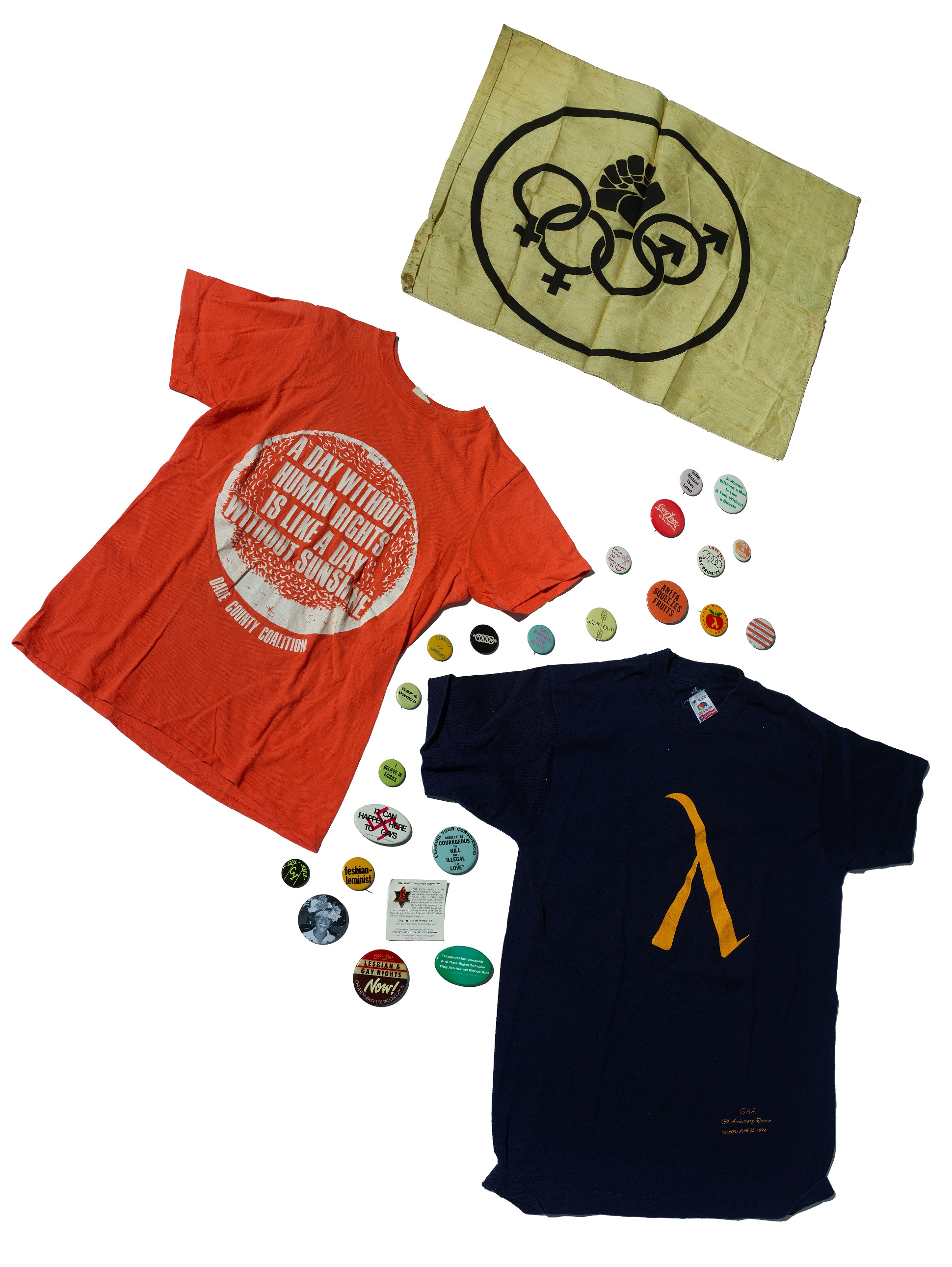An array of tshirts and pin back buttons lies on a white background