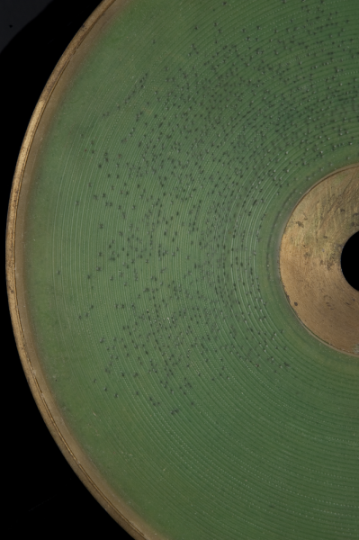 A close up of an emerald green disk with dark markings against a black background