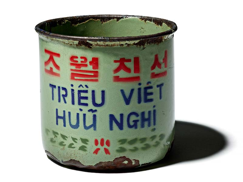A mint-colored metal cup with paint missing from the bottom and lip and writing in several colors on it.