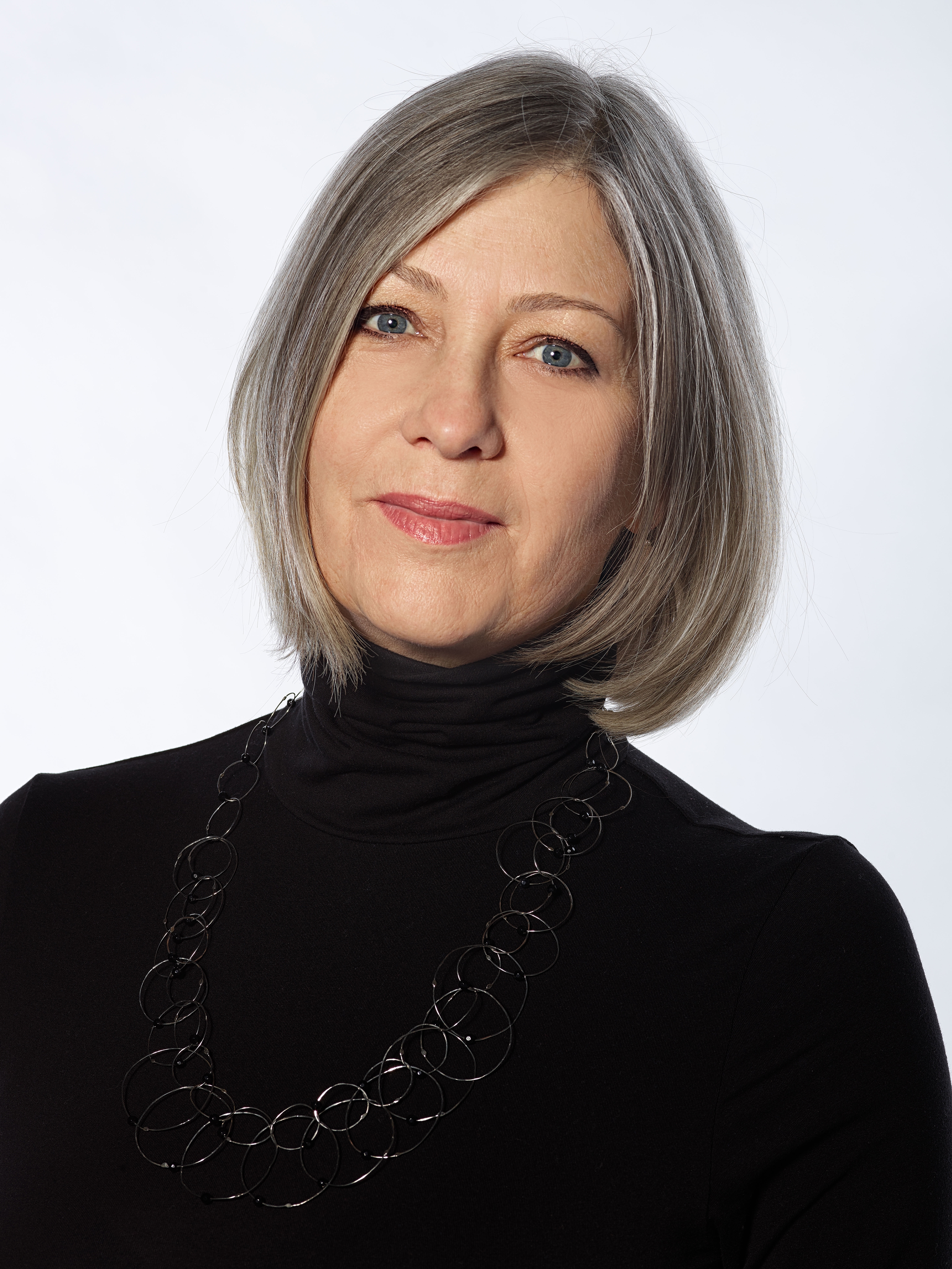 A headshot of a woman with silver hair in a black turtleneck