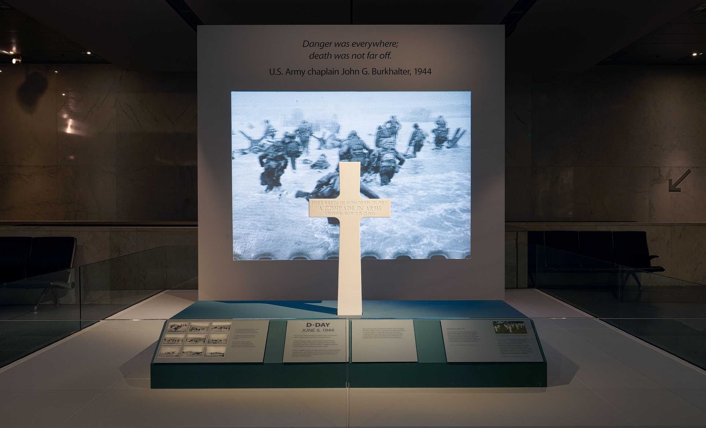 A view of a stone cross sitting on a platform in front of a projected image with text above it in a darkened space.