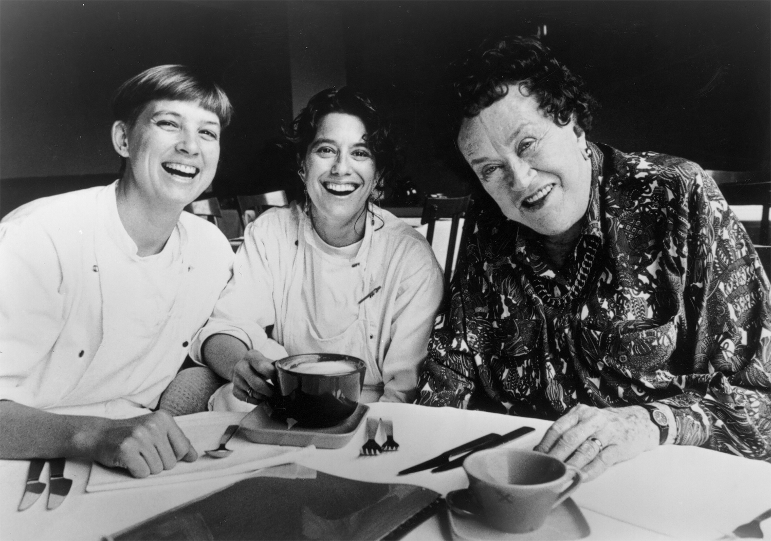 Three women sit around a table in a black and white photo. Two of them are dressed in white chef jackets and one of them is Julia Child
