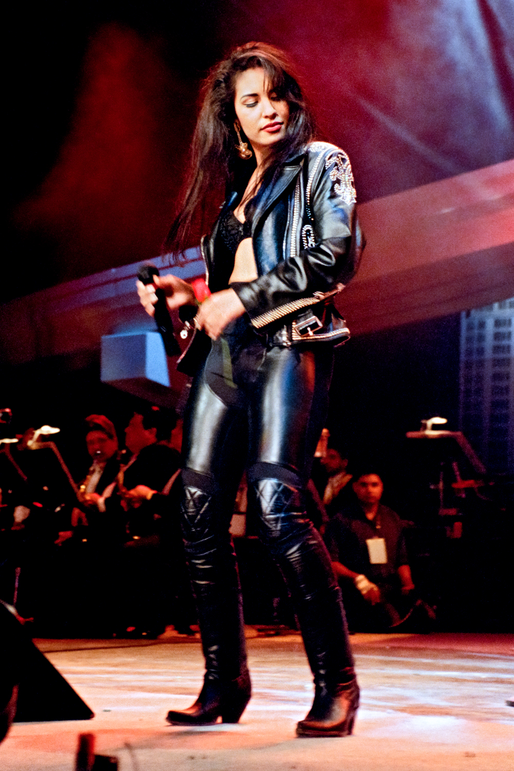 Selena on stage wearing black leather pants, jacket, and bustier