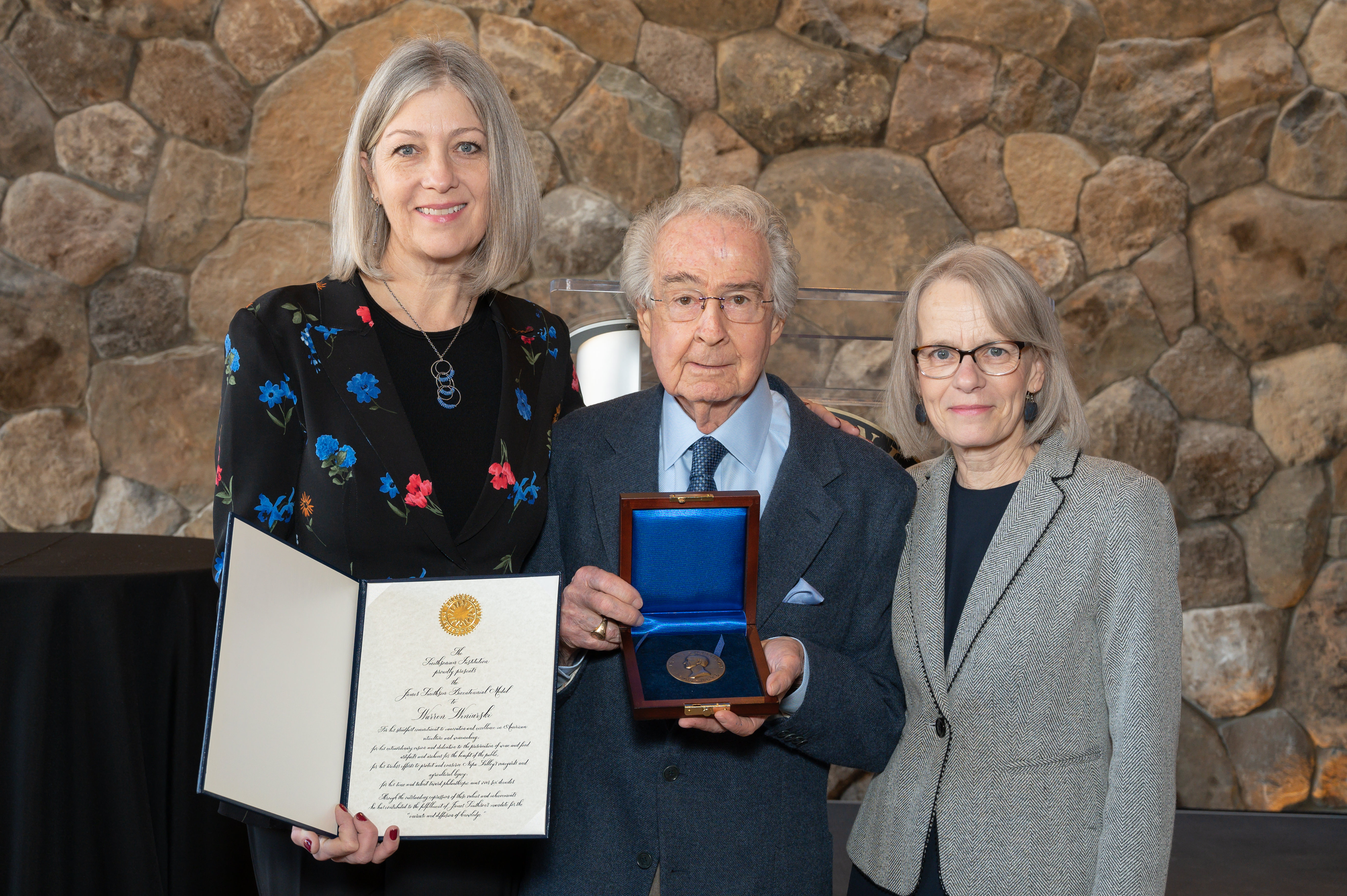 Three people standing. The woman on the left holds open a book with a certificate inside. The man in the center holds a medal on a blue silk-lined box.