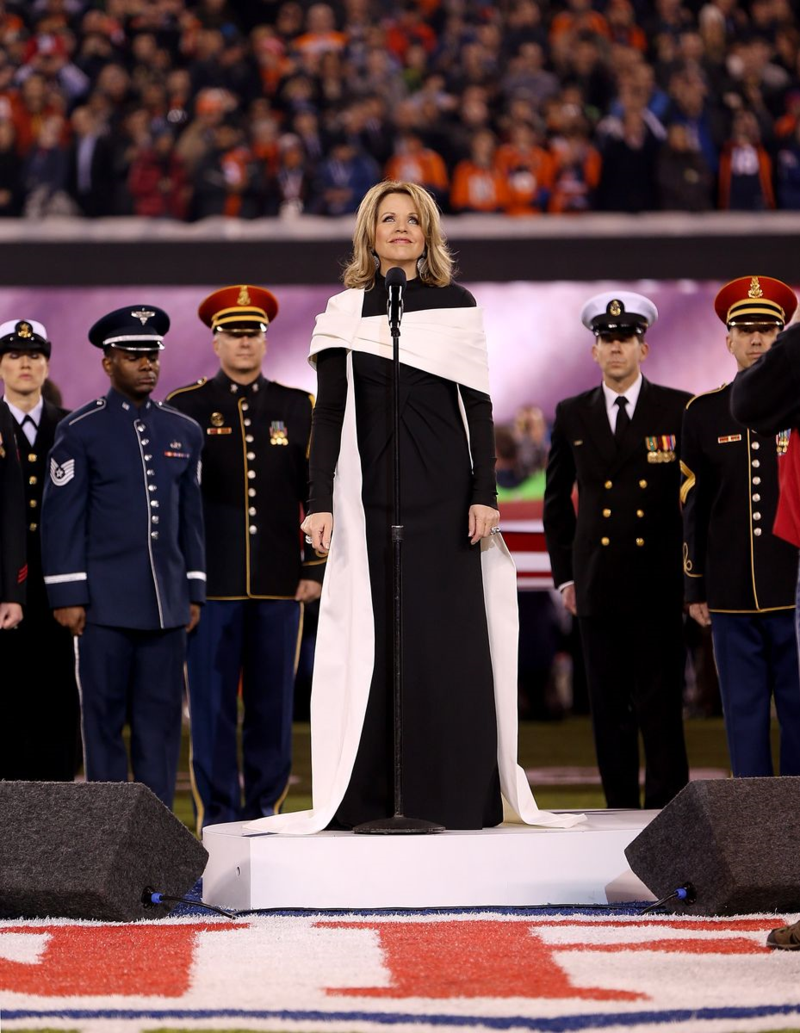 Renée Fleming on the field at halftime, backed by uniformed military members