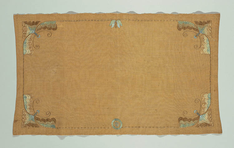 A coral place mat with multicolored embroidery around the border. At the bottom is the emblem of the Deerfield Society.