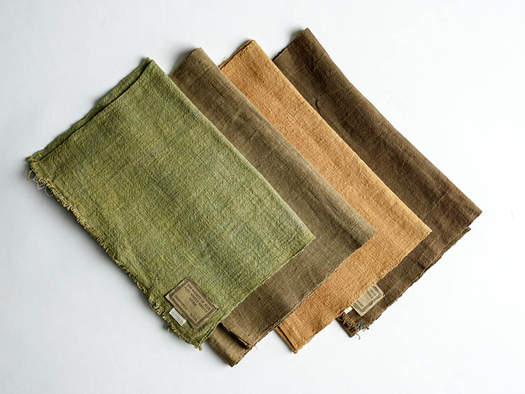 Four swaths of fabric, each dyed a different color: green, brown, coral, dark brown.