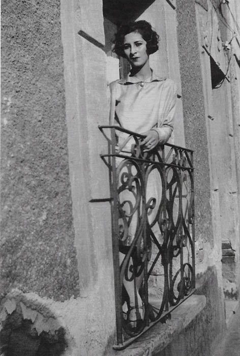 A black and white photograph of a woman leaning out a window