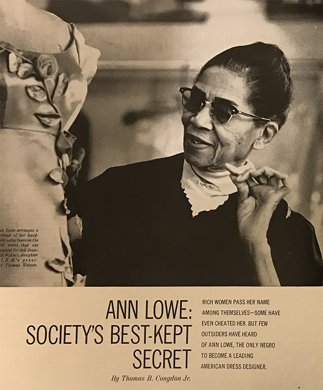 "Her hair pulled tightly back, wearing her signature sunglasses and a black dress, Ann Lowe examines a dress in a photograph from a magazine article. Below the photo, the title: ""Ann Lowe: Society's Best-Kept Secret."""