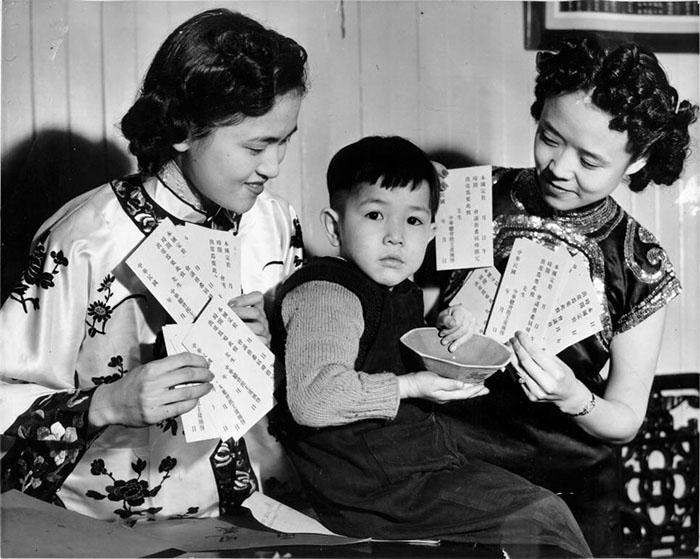 A black and white photograph of two women holding invitations to Rice Bowl Parties. A young boy holds a bowl.