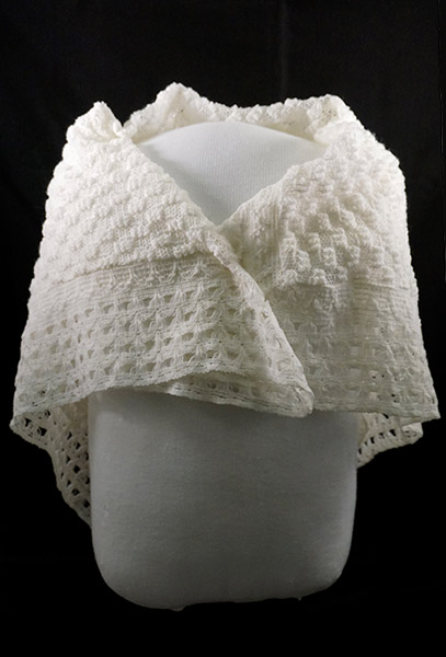 A photograph of a white crocheted shaw, wrapped around a form.
