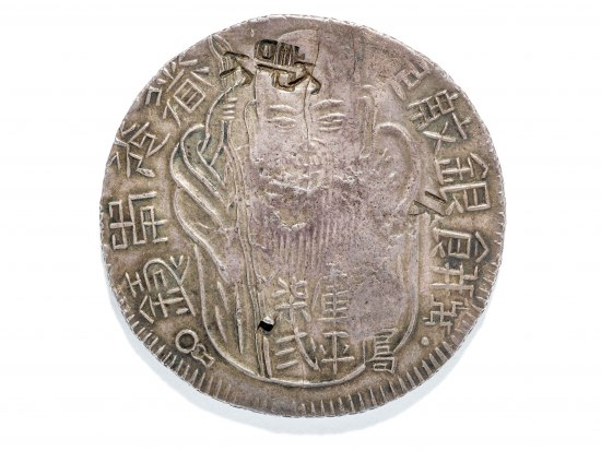 A silver coin with Chinese characters around the edges. There is a man's face in the middle though it is hard to make out because the coin is worn.