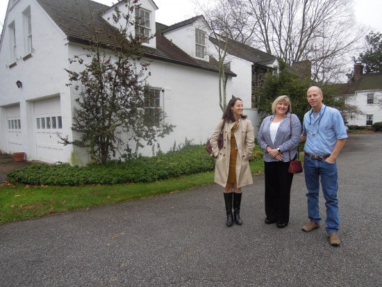 Two women and a man stand on a driveway running beside a white building/house. It is a cloudy day.