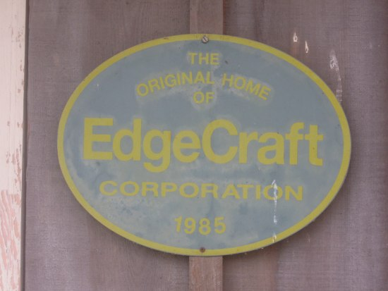 "An oval sign nailed to a wooden door or wall that is grey and yellow reading ""The Original Home of EdgeCraft Corporation 1985"""