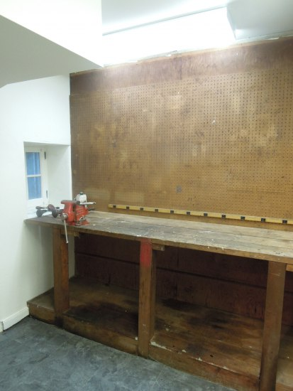 A small workroom with white walls and ceilings and a workbench against one wall that shows signs of use and age. There is a red object on the edge of the counter that is used to press items down.