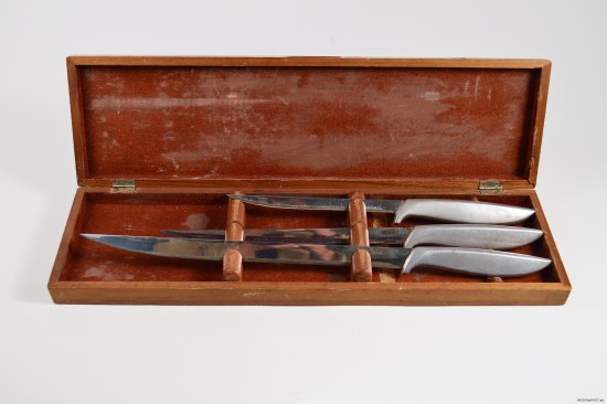 A wood box, long, thin and rectangular, sits open with three knives resting inside. Their blades are thin and sharp and they have metal handles
