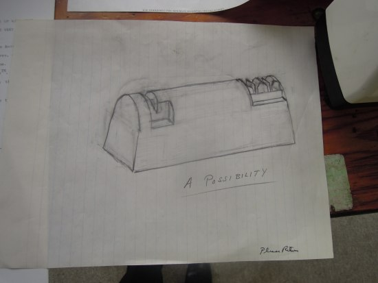 "A piece of lined notebook paper siting on top of a wood desk with a drawing of it of a small machine/contraption, which looks like an electronic knife sharpener. ""A Possibility"" is written underneath and it is signed in the righthand bottom corner"