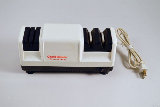 An electronic knofe sharpener rectangular in shape and encased in white plastic with a plug and cord. It has a black base with a switch and black sections where one places the knives.
