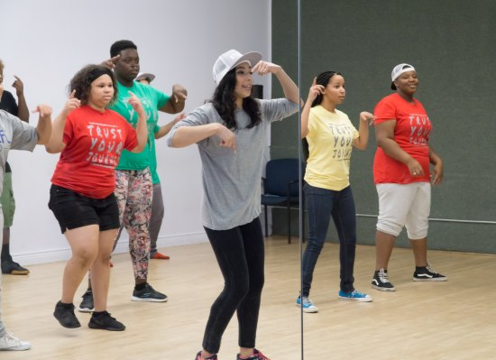 "A photography taken in the reflection of a mirror. An adult woman wearing a baseball cap, shows teenagers a dance move. Behind her, teenagers in colorful tee shirts reading ""Trust Your Journey"" follow along."